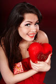 Girl with heart and gift box on red background. — Stock Photo