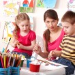 Stock Photo: Children painting with teacher in school.