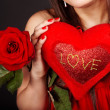 Girl with  heart and flower rose on red  background. — Stock Photo