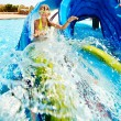 Child on water slide at aquapark. - Stock Photo