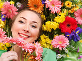 Young woman in flowers touching face. — Stock Photo