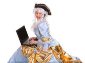 Woman in ancient dress with laptop and headset. — Stock Photo