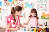 Child with teacher draw paints in play room. — Stock Photo