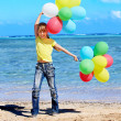 Child playing with balloons at the beach — Stock Photo #9302809