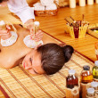 Woman getting massage in bamboo spa. - Stock Photo