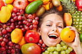 Girl in group of fruit. — Stock Photo
