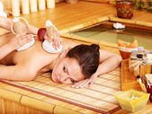 Woman getting massage in bamboo spa. — Stock Photo