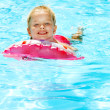 Child sitting on inflatable ring in swimming pool. — Stock Photo