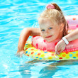 Child sitting on inflatable ring in swimming pool. — Stock Photo #9497758