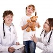 Two paediatrician treat happy child. - Stock Photo