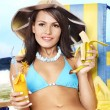 Girl in bikini drink juice through a straw. — Stock Photo