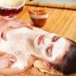 Girl having clay body mask apply by beautician. — Stock Photo #9504633