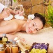 Stock Photo: Womgetting thai herbal compress massage .