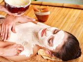 Girl having clay body mask apply by beautician. — Stock Photo