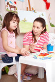 Child playing with teacher in preschool. — Stock Photo