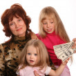 Grandmother with granddaughters, takes money. — Stock Photo