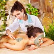 Girl having clay body mask apply by beautician. - Stock Photo