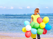 Child playing with balloons at the beach. — Stock Photo