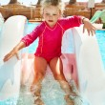 Child on water slide at aquapark. — Stock Photo #9862184