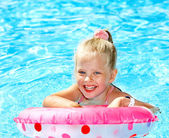 Child sitting on inflatable ring in swimming pool. — Zdjęcie stockowe