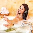 Woman listening to music in bubble bath. — Stock Photo #9870875