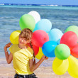 Child playing with balloons at the beach - Stockfoto