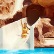 Child on water slide at aquapark. - Zdjcie stockowe