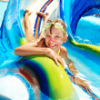Child on water slide at aquapark. Summer holiday. — Stock Photo