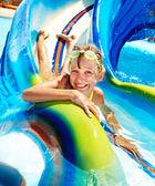 Kind op wasser rutsche op aquapark. zomervakantie. — Stockfoto
