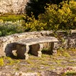 Old stone carved bench in garden — Stockfoto