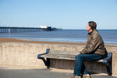 Senior man looking out over beach at Southport — Stock Photo