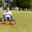 Senior man on zero turn lawn mower on turf — Stock Photo #10194378
