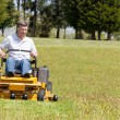 Senior man on zero turn lawn mower on turf — Stock Photo #10194384