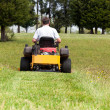 ストック写真: Senior man on zero turn lawn mower on turf