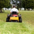 Foto de Stock  : Senior man on zero turn lawn mower on turf