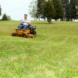 Senior man on zero turn lawn mower on turf — Stok fotoğraf