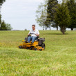 Stock Photo: Senior man on zero turn lawn mower on turf