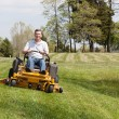 Senior man on zero turn lawn mower on turf — Stock Photo #10194503