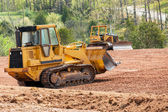Large earth mover digger clearing land — Stok fotoğraf
