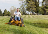 Senior man on zero turn lawn mower on turf — Stock Photo