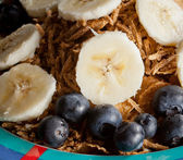 Slices of banana and blueberries on cereal — Stock Photo