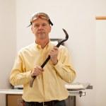 Senior man holding a crowbar — Stock Photo