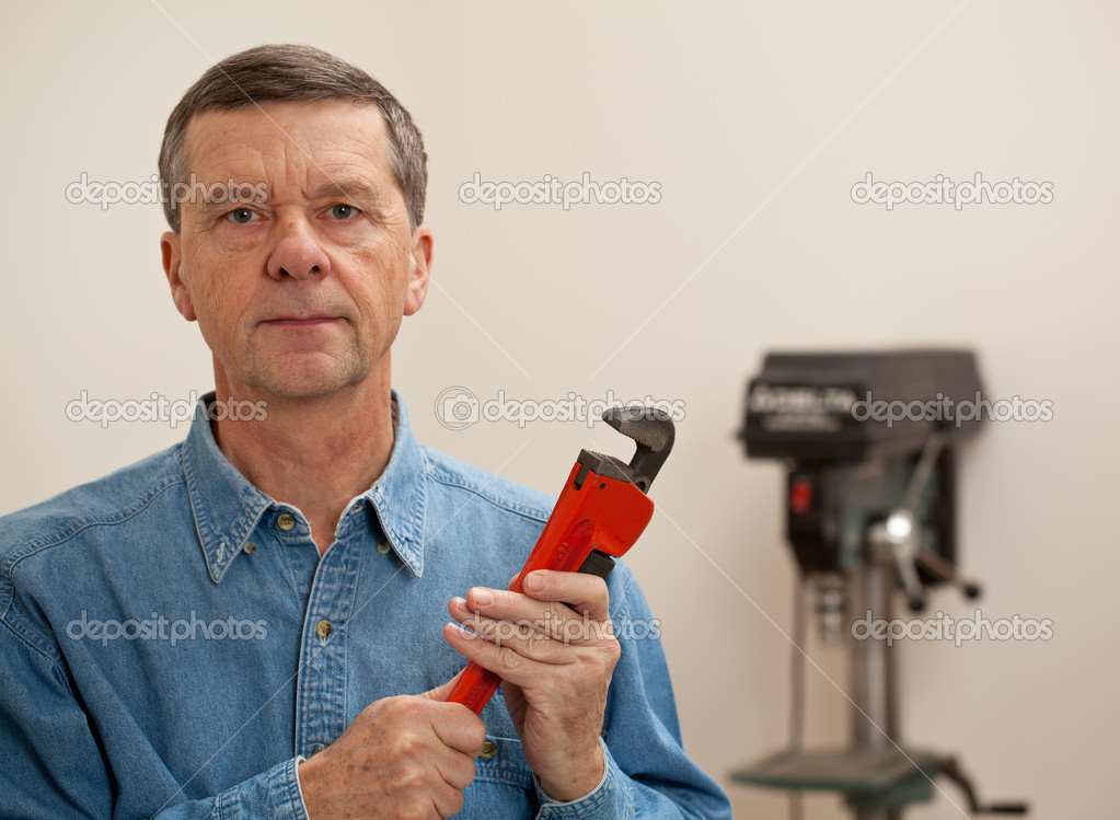 Senior male in a home workshop facing the camera and holding a large wrench — Stock Photo #8275609