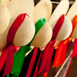 Row of straw hats with ribbons — Stock Photo