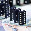 Standing dominoes on bank notes — Stock Photo