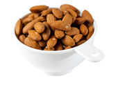 Raw organic almonds in measuring cup — Stock Photo