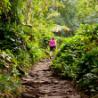 Girl hiking Kalalau trail in Kauai - Stock Photo