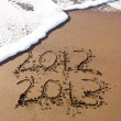 2012 and 2013 written in sand with waves — Stock Photo