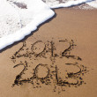 Stock Photo: 2012 and 2013 written in sand with waves