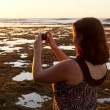Girl taking photo of sunset on phone — Stock Photo